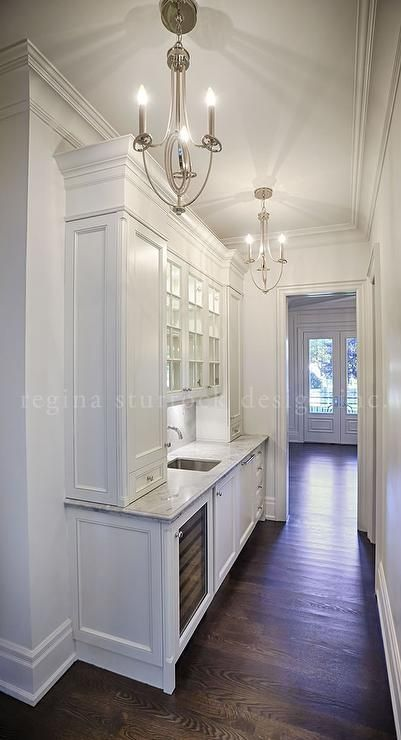 A white butler's pantry features two silver chandeliers illuminating white cabinets paired with gray quartzite countertops fitted with a sink under lighted glass front cabinets.