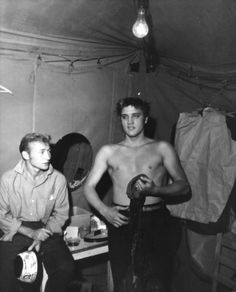 A barechested Elvis Presley and friend and actor Nick Adams backstage at the famed singer's homecoming - Tupelo, MS September 1956