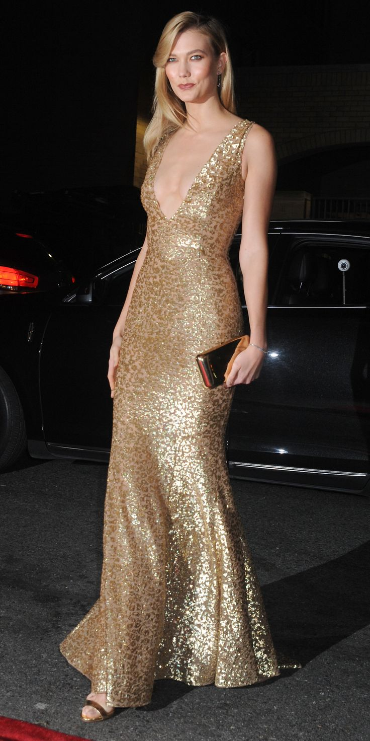 Look of the Day - Karlie Kloss glittered at the L'Oreal Paris Women of Worth Celebration, lighting up the red carpet in a gold sequined deep-V Michael Kors Collection gown, complete with a gold Judith Lieber Couture clutch and Eva Fehren jewelery.