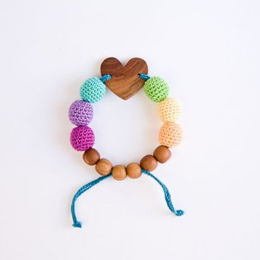 Teething Bracelet - Snow Rainbow with Heart Pendant - This bracelet will be a great match to the Snow Rainbow necklace or simply a wonderful addition to your jewelry collection! It is completely natural and stylish. The heart and the beads are both made of high quality apple wood. The bracelet is completely safe for the baby to chew on and it could be used as a teething toy for your little one.