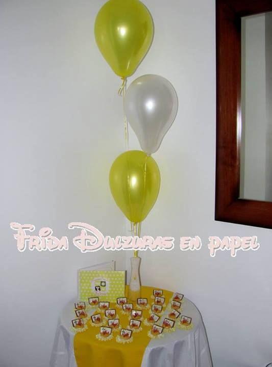 Mesa de souvenirs con globos y mantelería a tono