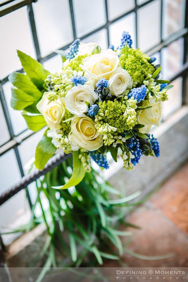 Bruidsboeket met witte en crème rozen, opgefleurd met blauwe druifjes.