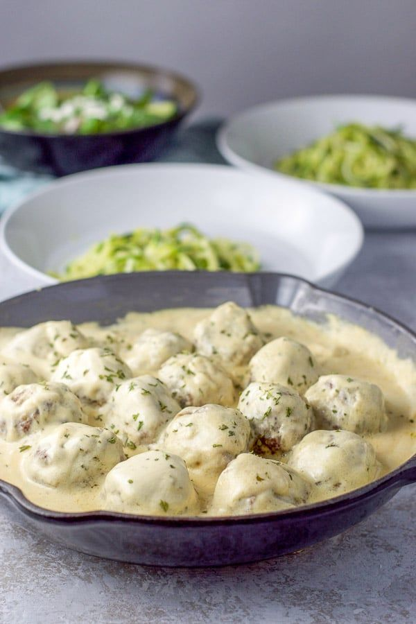 Pan Of Swedish Meatballs With Sour Cream Sauce Front And Center With Two Plates Of Zoodles In The Bac Sour Cream Gravy Recipe Cream Sauce Recipes Clean Recipes