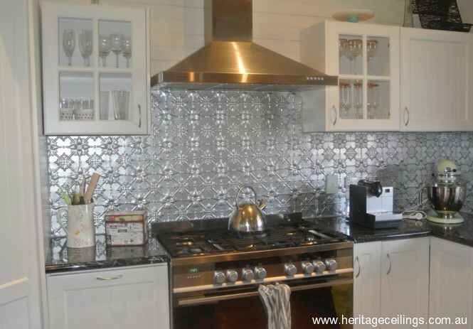 Pressed metal splash back in silver with white shaker style cabinetry. Photo credit- heritageceilings.com.au