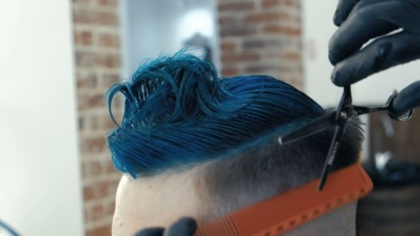 Barber Cutting Hair with Scissors and Comb, a Client Is a Young Caucasian Man. Bright Blue Hair.