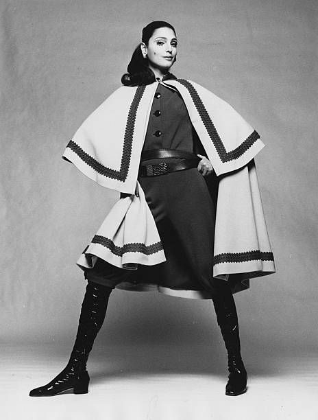 Model stands wearing a wool jersey braid trimmed cape with a jumpsuit all by Laura Aponte with Dal Co boots in Corfam Hair by Alba e Francesca