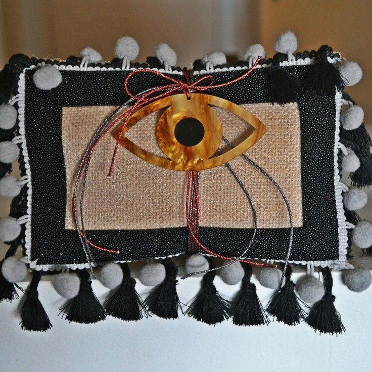 Χειροποίητο γούρι μαξιλάρι από λινάτσα με κορδέλα μαύρη χαβιάρι, πον πον και φούντες και στη μέση δεμένο κοκκάλινο μαύρο μάτι