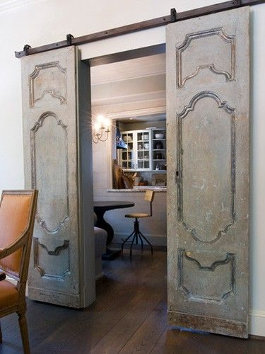 Vintage Doors hung with barn door style hardware.  If I happen  to find such interesting doors, I could add them after the house is finished, between living room and dining room/kitchen. Even if they both stayed open 90% of the time (longer toprail than shown here would be necessary), they would be a nice decorative addition, easily installed.