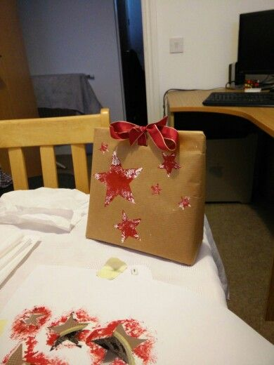 Christmas wrapping using DIY stencils and painted using paint tester pots and tissues on brown paper wrapping.