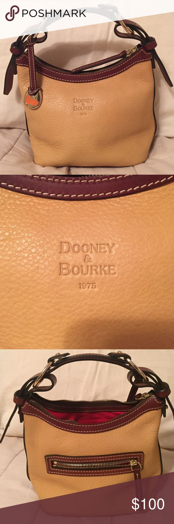 Dooney & Bourke Purse **Authentic** Tan and brown leather  small purse with red interior. Outside zipper, inside zipper, leather pocket and clip. Small size bag. No marks or any kind, only used a handful of times. Dooney & Bourke Bags