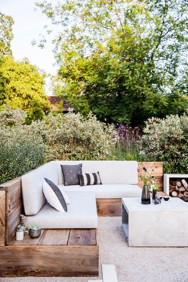 Уютный дворик с намеком на стиль лофт, на что намекает угловая деревянная скамья с мягкими подушками и бетонный журнальный столик. .