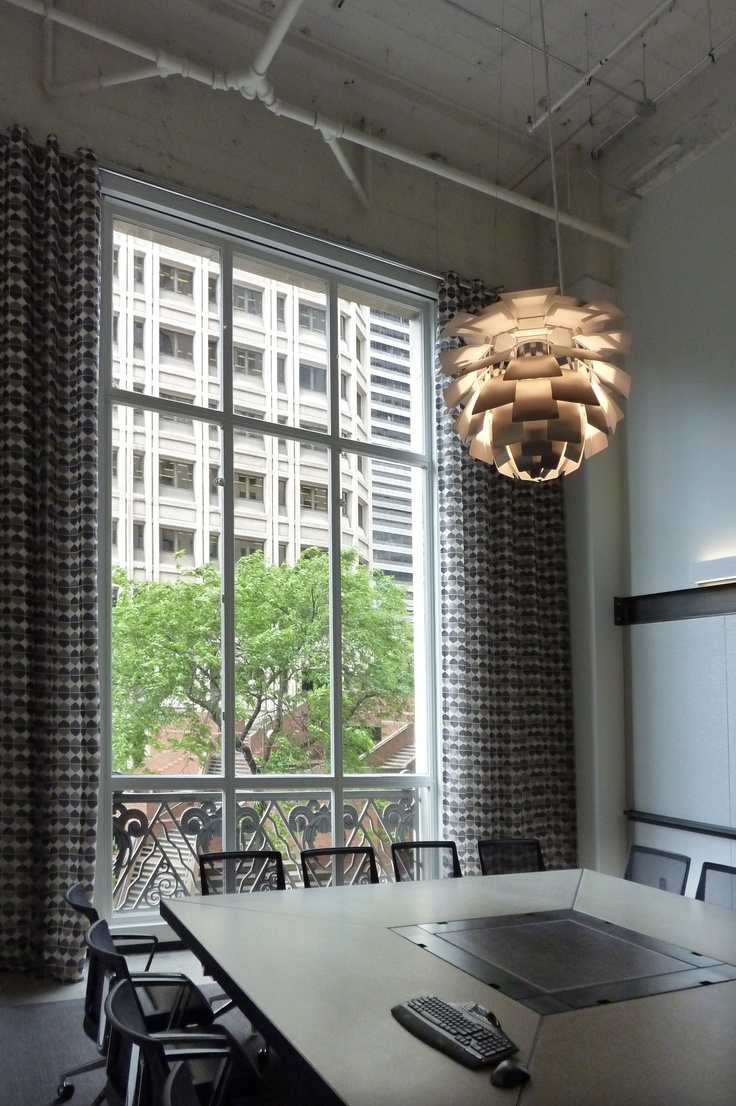 """""""Mies"""", the main conference room at EHS. Louis Poulsen artichoke light fixture and bespoke concrete, steel, and leather conference table. Drapes by Knoll."""
