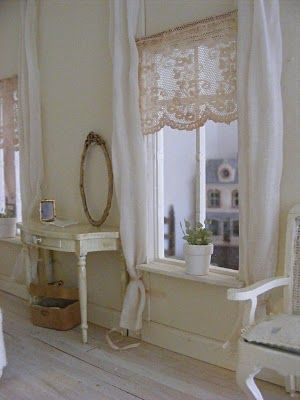 Lace curtains with same color curtains (low tiebacks) as the wall on each side of the windows, oval mirror, off white desk, basket, one flower in each window, white chair ~!~