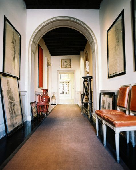 Long Hallway - A hallway decorated with leather chairs, framed art, lanterns, and busts