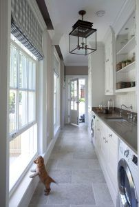 Mudroom Laundry Room Combined. Mudroom Laundry Room. Great mudroom laundry room design featuring quartz countertop and natural stone floor tiles. Lighting is Honore Lantern by Suzanne Kasler in Antique Zinc. #laundryroom #mudroom #LaundryRoomMudroom #LaundryRoomMudroomCombined #HonoreLantern #SuzanneKasler Hayburn & Co
