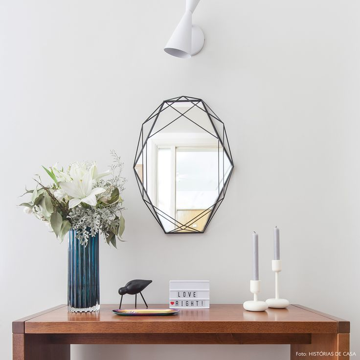 Hall de entrada tem aparador de madeira, espelho e objetos minimalistas.