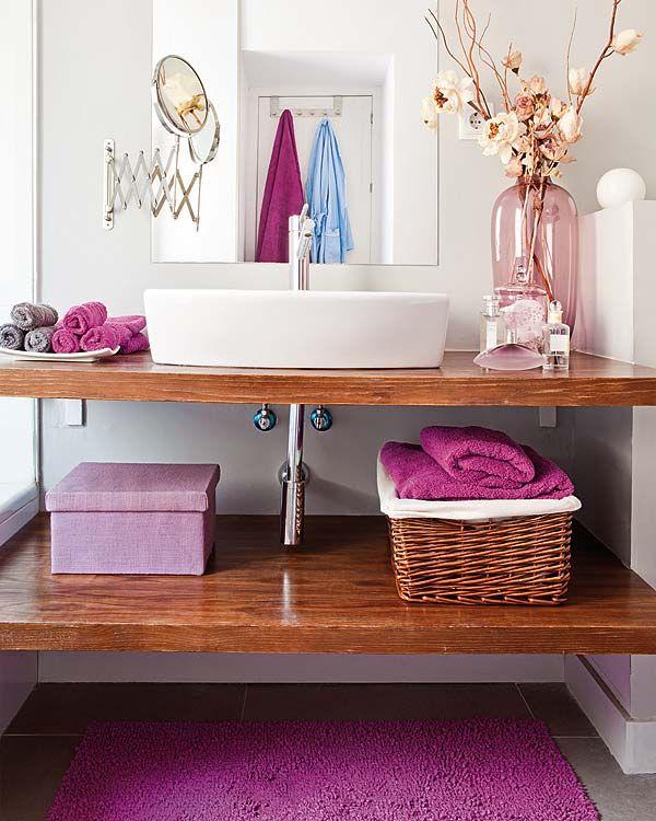 Banheiro em branco com detalhes coloridos nas caixas, toalhas e vaso