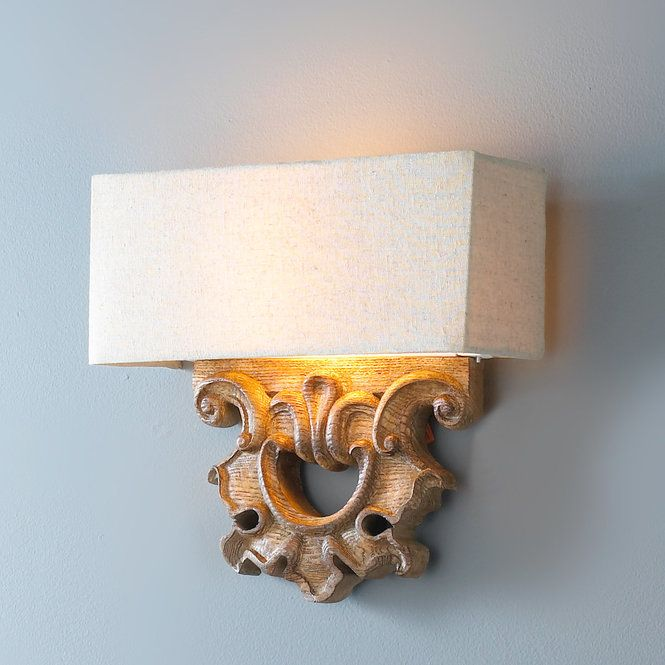 """With a sophisticated approach to classic French design, this wall sconce blends refinement with a casual feel. Its clean, architecturally influenced design combines timeless carvings in a rich Patina Oak finish with a crisp beige fabric shade. ADA Compliant. Requires 2 - 60 watt candelabra base sockets. (11.5""""Hx12""""Wx4""""D)"""
