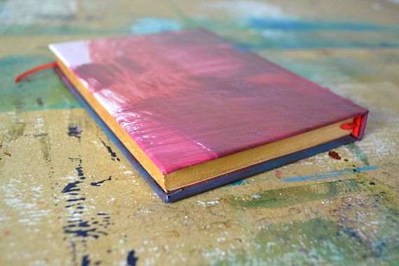If you are looking for a pocket-sized journal thats a little bit different, look no further! This beautiful little book holds 100 pages of thick, white, unlined 140gsm cartridge paper, suitable for all media. This book is complete with unique hand-painted cover, metallic page edges and ribbon page marker. Whether you want to jot down ideas, keep shopping lists or sketch on the go, this little, hand-painted, handcrafted journal is completely unique, just like you
