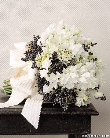Clusters of blue-black privet berries stand out against sweet peas, narcissus, and star-shaped ornithogalum in a charmingly rustic bouquet tied with ivory grosgrain ribbon.