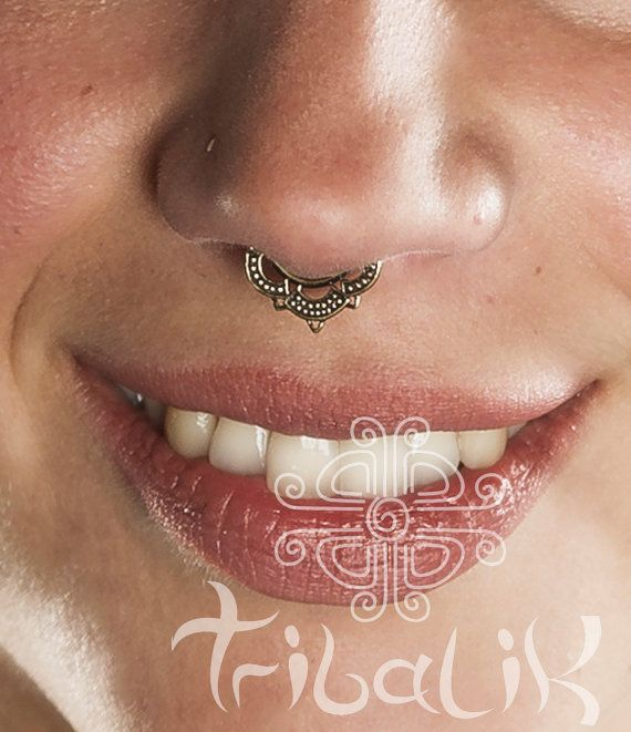 This stunning septum piercing features a beautiful and unique design.  Choose wire from 1mm1.6mm / 14 gauge - also available for non-pierced nose. The inside space (wearable length) is 9mm / 3/8 Total length is 18mm / 11/16 Total width is 18mm / 11/16 Made in tribal brass.  This is made with brass not surgical steel so please polish with natural polish your skin can tolerate to bring out the shine. Surgical steel is advised for constant wear and certainly for healing piercings. These are in…