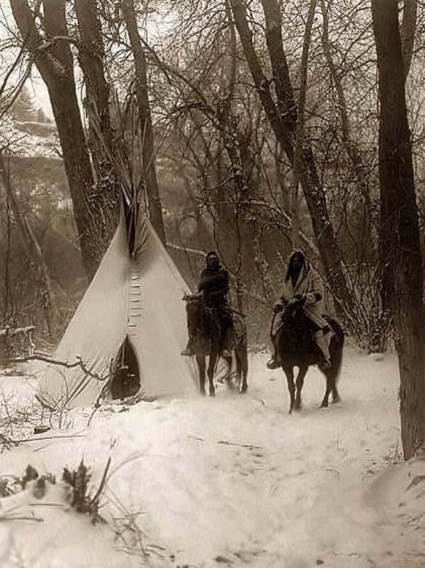 Native American Indians photographed riding their horses in front of their TeePees in the harsh Winter