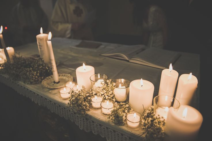 A picture of the altar decorated with white candles and baby's breath