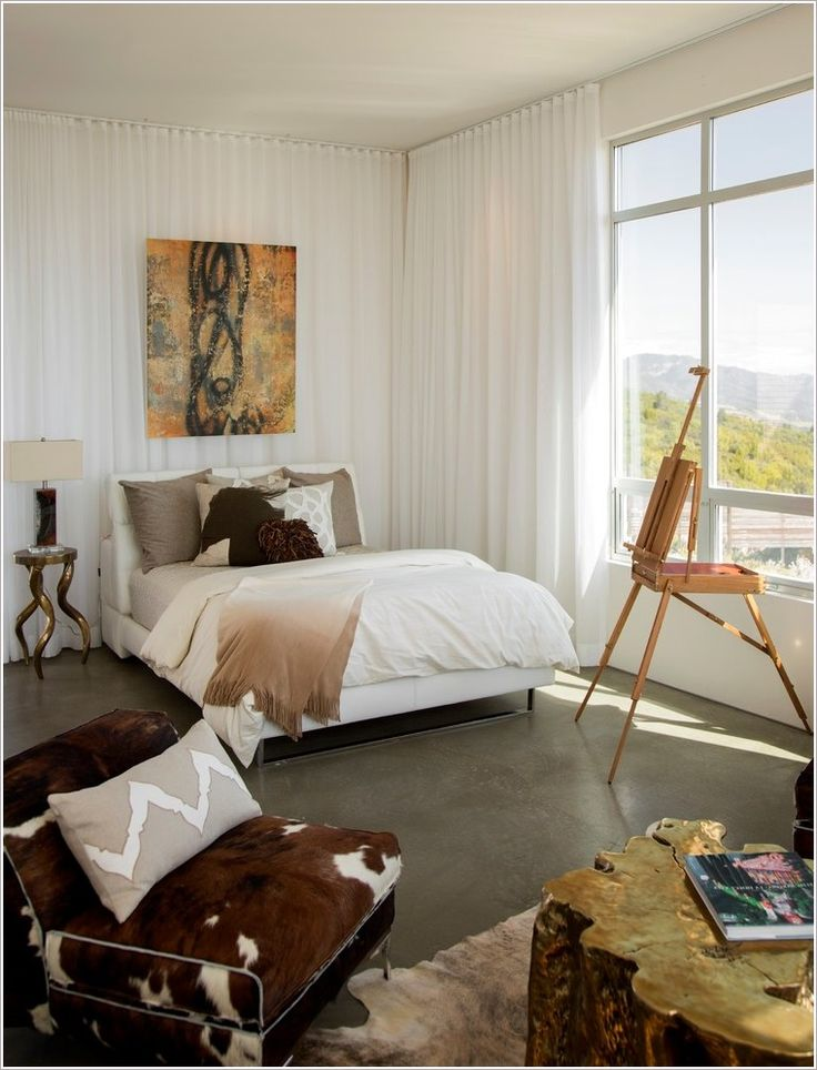 San francisco bedding coffee table cowhide chair cowhide rug cushions easel neutral colors painting picture windows pillows polished concrete floor side table table lamp upholstered bed white curtain
