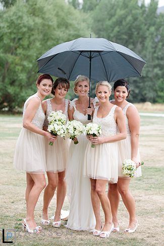 Rainy wedding with Bride and Bridemaids under umbrella