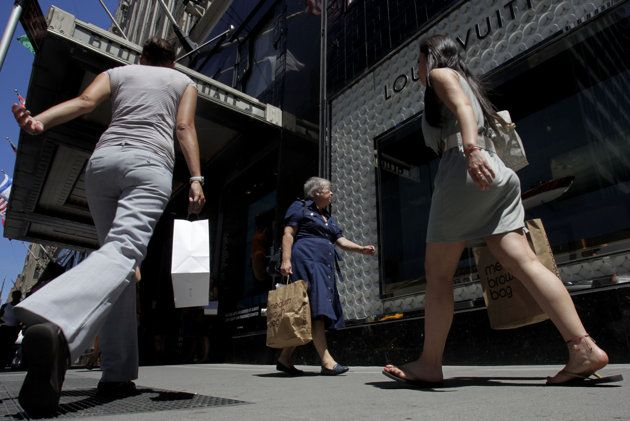 Women with shopping bags cross paths in front of Bloomingdales in New York, Tuesday, July 5, 2011. (AP Photo/Seth Wenig)