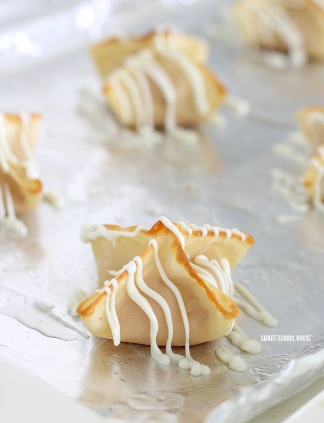 Strawberry Cream Cheese Wontons - 4 ingredient sweet and fluffy strawberry cream cheese mixed with buttery soft baked wonton flavor then drizzled in white chocolate.