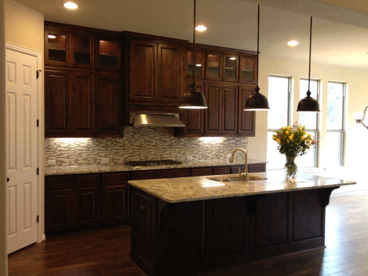 Knotty Alder Cabinets in Verona, Glass Display to the ceiling with illumination from puck lights, Pietra Cristal Crema Strato Backsplash, Thunder Crème Granite Tops, Prestige Oil Rubbed Bronze Bell Pendants