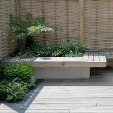 low maintenance decking and small seating area/bench in corner of garden