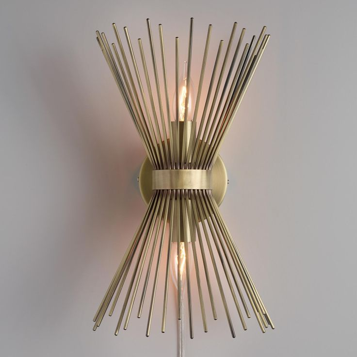 Crafted of iron with a matte brass finish, our exclusive dual-light wall sconce features a starburst of rods that illuminate with a warm glow. Both a mid-century modern wall art piece and a lighting solution for nightstands or reading nooks, it includes a plug-in cord for easy installation with no hardwiring required. www.worldmarket.com #WorldMarket #FallHomeRefresh