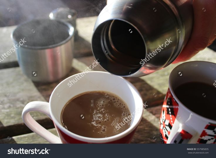 coffee cups mug and thermos bottle over wooden table outdoors, the steam from the hot coffee