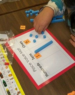 Instead of using plastic cubes, use candy corn with the place value mats that you already have.
