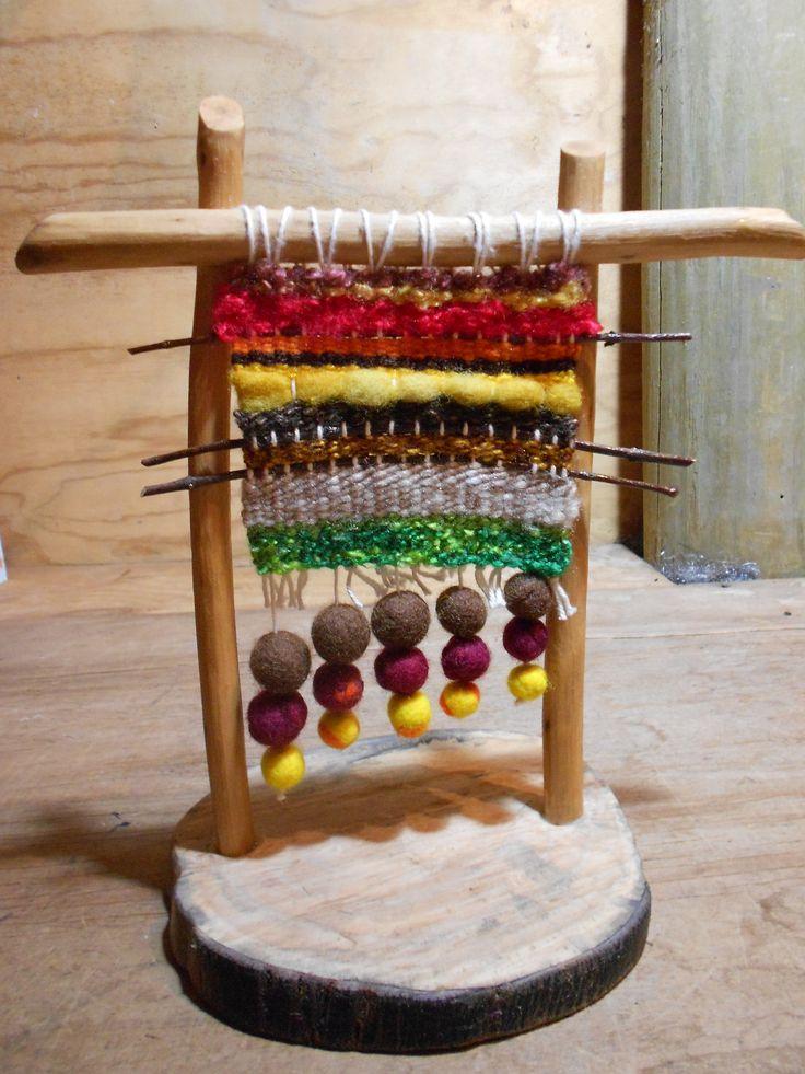 Pequeño telar de pie. Para decorar una mesa, velador o escritorio. Aplicaciones de variadas lanas, ramas y bolitas de vellón.