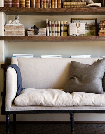 In the living room, a tailored linen-covered settee relaxes with a feather-stuffed bench-style seat cushion.   - HouseBeautiful.com