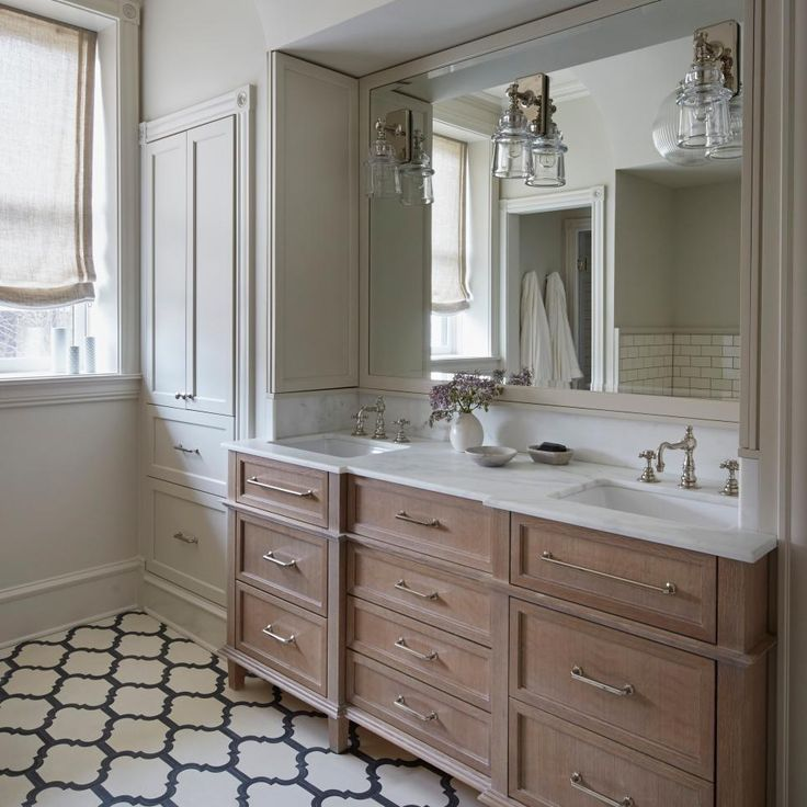 The fresh-feeling design in this bathroom combines concrete tiles with bleached oak and painted cabinets for a feel that's organic and peaceful. Lighting: Waterworks; Tiles: Popham Design