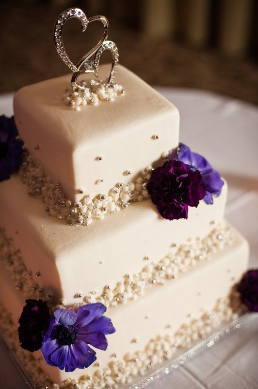 wedding cake is highlighted by purple anemones and burgundy carnations.