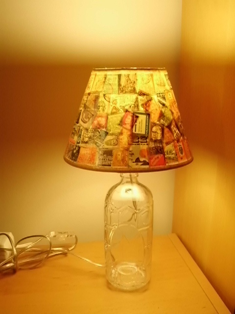 Vintage postage stamps on a used bottle transformed to a unique lampshade