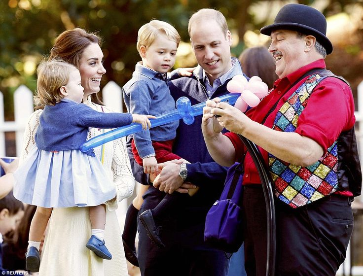 Held in their parents' arms, Princess Charlotte and Prince George take a closer look at a balloon artist at work