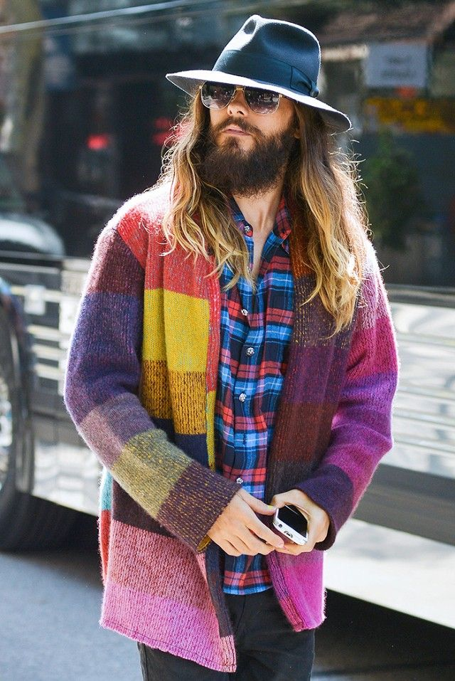 Jared Leto looking ultra cool I. A brimmed hat, plaid shirt, and colorful coat