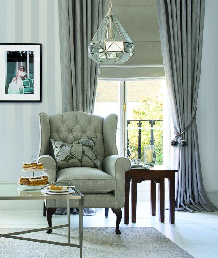 Модный интерьер в сером цвете, обои в полоску, шелковые шторы, геометрическая люстра, кресло с декоративной подушкой