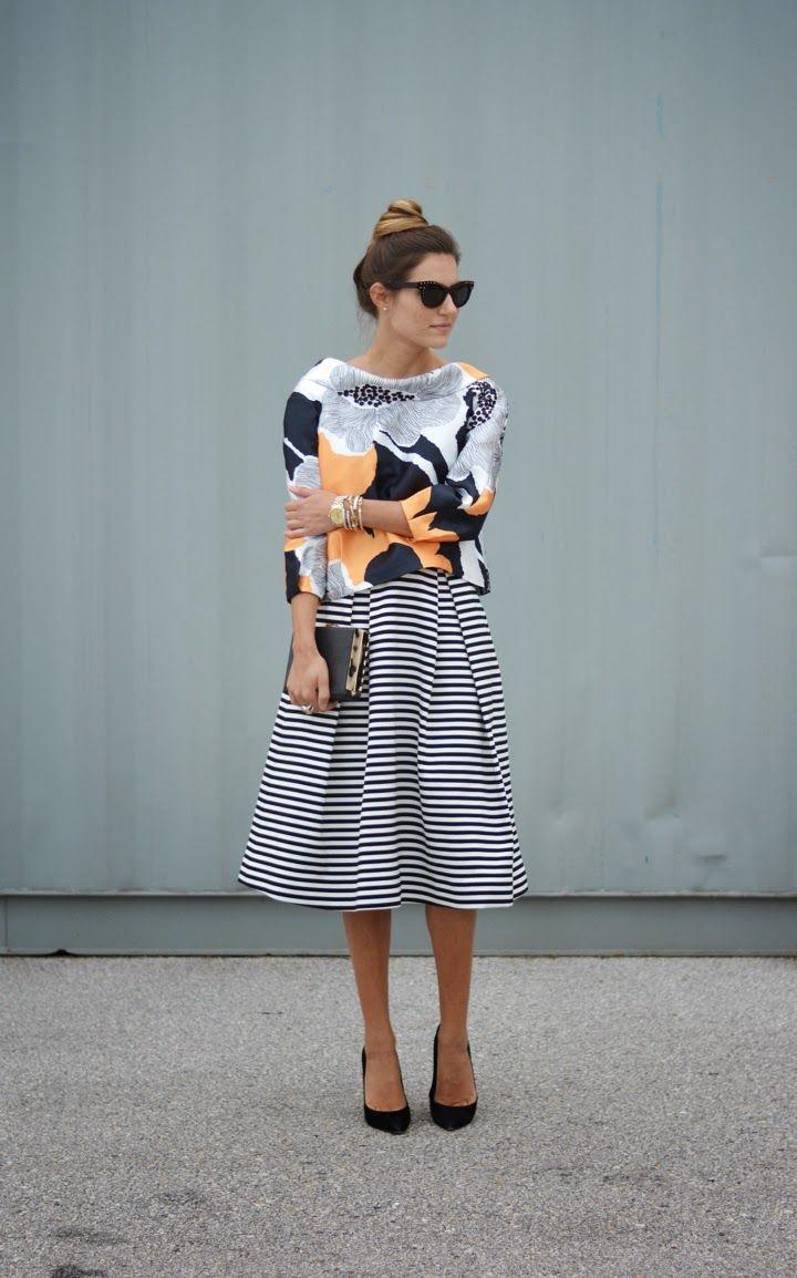 inspiração street style para um mix de estampas com blusa de manga longa floral, saia mídi listrada, scarpin preto, clutch preta e óculos gatinho preto