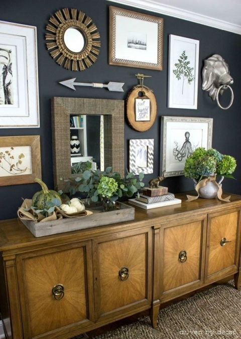 Eclectic-gallery-wall-on-dark-charcoal-walls-console-decorated-will-pumpkins-and-fall-flowers-600