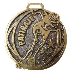 Medalla genérica de patinaje en acabados envejecidos y brillantes, con placa de marca en posterior y cinta para colgar
