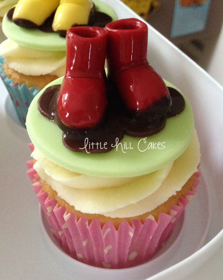 Peppa Pig muddy puddle cupcakes with shiny little wellies. Twelve pairs of wellies in yellow, red and blue (the colours of Peppa, George & Mummy Pig's wellies) for a Peppa Pig themed 3rd birthday party.