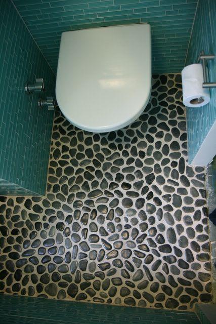 Piso del baño totalmente hecho de piedras pequeñas