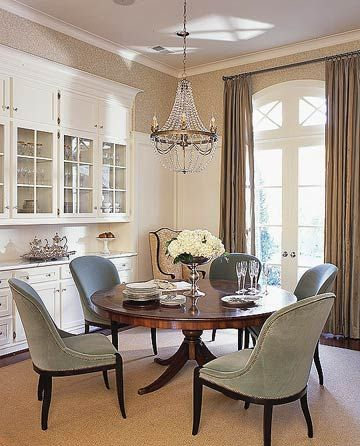 Sophisticated Kitchen or Dining Room The built-in china cabinet behind the dining set has glass doors to display fine china and closed storage below. French doors enable sunlight to fill the room, while classic drapes allow privacy when desired. The round dining table makes for an intimate gathering place. Upholstered chairs provide comfort and style, and are accented to match the table